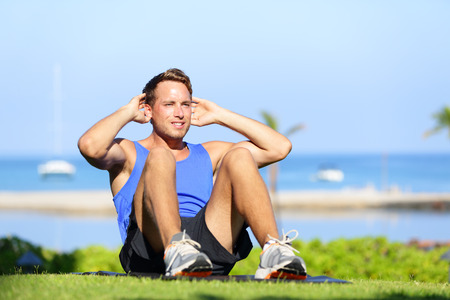 situps: Man exercising sit-ups outside. Male fitness model training situps exercise outdoor in summer during workout. Handsome fit muscular sport model.