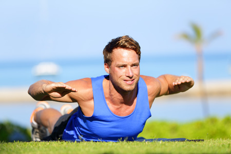 Fitness man training back extension exercise outdoor. Fit male sport athlete exercising lower back during cross training workout outside on grass in summer. Fit handsome muscular sports model. photo