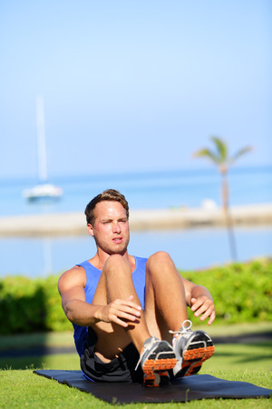 situp: Training fitness man doing sit-ups exercise for abs outdoors. Fit male athlete cross training jackknife sit up during workout. Muscular handsome young caucasian man working out outside.