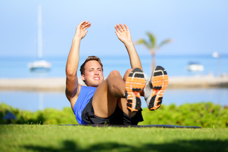 sit ups: Fitness man doing sit-ups exercise for abs outdoors. Fit male athlete cross training jackknife sit up during workout. Muscular handsome young caucasian man working out outside.