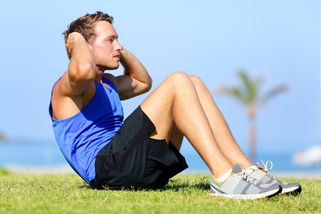 Sit-ups - fitness man training sit up outside in grass in summer. Fit male athlete working out cross training exercising. Caucasian muscular sports model in his 20s. Stock Photo