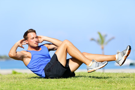 sit: Sit ups - fitness man exercising sit up outside in grass in summer. Fit male athlete working out cross training in summer. Caucasian muscular sports model in his 20s.