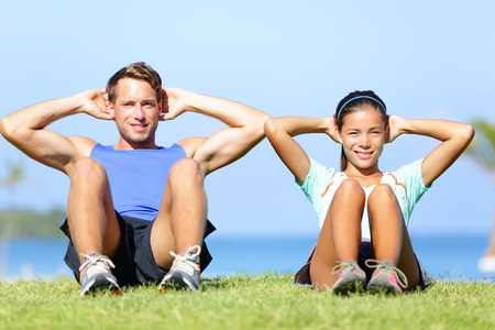 core: Sit ups - fitness couple exercising sit up outside in grass in summer. Fit happy people working out cross training. Beautiful young multiracial couple, Asian woman, Caucasian man.