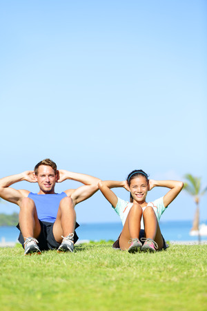 situp: People exercising - Couple doing sit ups outdoors. Fitness couple doing situps exercise during outside cross training workout. Happy young multiracial couple, Asian woman, Caucasian man. Stock Photo