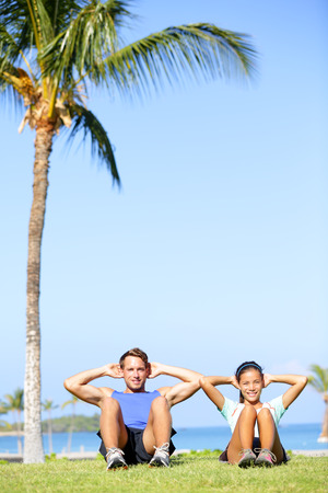 People training sit ups outside. Fitness couple doing situps exercise during outdoor cross training workout. Happy young multiracial couple, Asian woman, Caucasian man. Stock Photo - 26345701