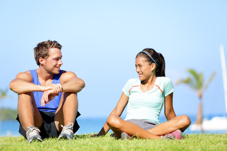 Sport fitness couple relaxing after training outdoor. Young people talking sitting in grass after running and training exercise outside in summer. Caucasian man sports model and Asian woman model. photo