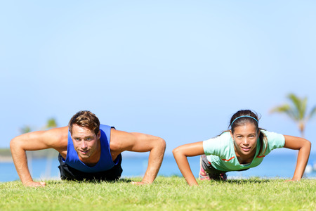 Sport fitness couple doing push ups outdoor. Young athletes doing pushups exercise outside on grass in summer. Caucasian man sports model and Asian woman fitness model doing push-ups workout. photo