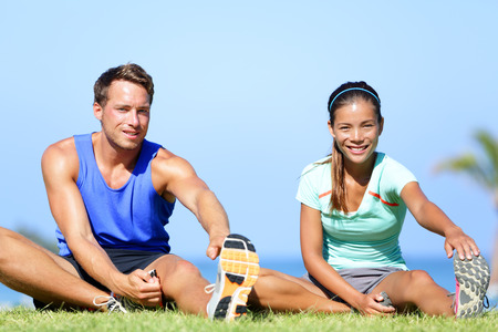 man working out: Stretching exercises - Fitness couple outside doing stretches exercise. Fit woman and man doing hamstring leg stretching training in summer. Beautiful multiracial couple. Stock Photo