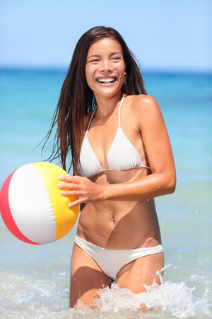 Beach woman playing with ball having fun laughing happy. Young mixed race asian caucasian woman playing ball in sea waves - smiling, enjoying the sun. Big Island, Hawaii photo