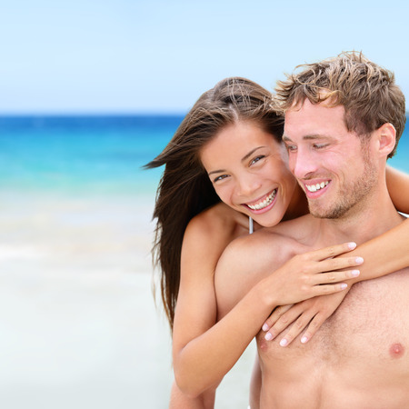 man carrying woman: Happy couple on beach in love having fun together on travel vacation holidays on tropical beach. Beautiful interracial couple, Asian woman, Caucasian man.