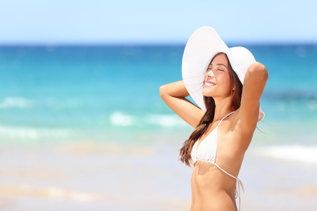 Beach woman relaxing on travel vacation smiling happy and cheerful in summer sun. Beautiful multiracial Asian Chinese  Caucasian woman wearing white beach hat and bikini on tropical paradise beach.
