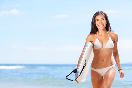 Woman surfer girl beach. Sexy woman surfer girl body surfing on beach. Beautiful woman laughing having fun bodyboarding under sun and blue sky during summer travel vacation, Maui, Hawaii, USA. photo