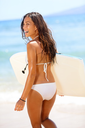 Sexy woman surfer girl body surfing on beach. Beautiful woman laughing having fun bodyboarding under sun and blue sky during summer travel vacation, Maui, Hawaii, USA. Mixed race Asian bikini babe. photo