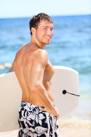 Handsome male surfer portrait on summer beach. Bodyboarding surfing man good looking standing with bodyboard surfboard during vacation holidays getaway. Caucasian water sport model in his 20s. Stock Photo