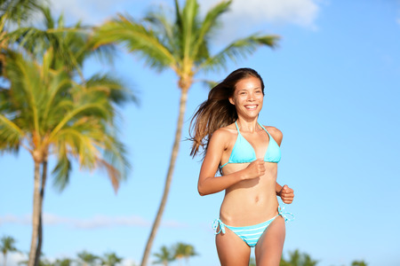 hawaiian girl: Bikini woman running on beach smiling happy and on tropical summer beach with palm trees. Beautiful sexy mixed race Asian Caucasian girl in her 20s. Image from Hawaii. Stock Photo