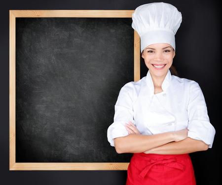 Chef showing menu blackboard. Woman in front of blank menu blackboard. Happy female chef, cook or baker by empty chalkboard menu display wearing chef whites uniform and hat photo
