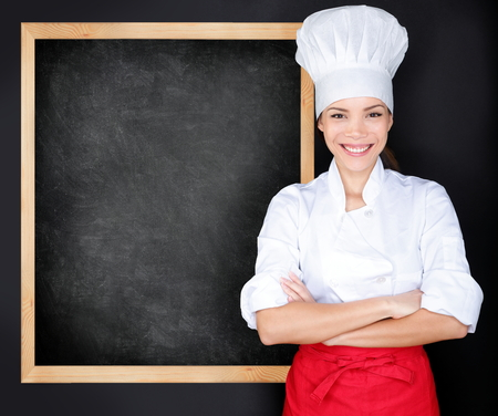 chefs whites: Chef showing menu blackboard. Woman in front of blank menu blackboard. Happy female chef, cook or baker by empty chalkboard menu display wearing chef whites uniform and hat