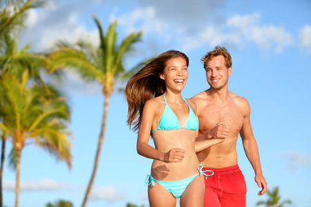 Couple having fun on beach vacation travel laughing happy running together playful and joyful. Woman in bikini and man in swimwear. Beautiful interracial lovers in love on honeymoon on Hawaii. Stock Photo