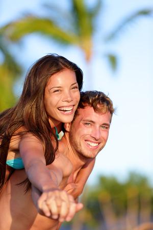 Couple fun on beach. Man giving piggyback ride to girlfriend on beach. Beautiful interracial couple in love. Asian woman, Caucasian man on Hawaii.