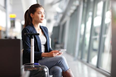 travel: Mulher viajante de passageiros no aeroporto esperando para viagens aéreas usando tablet telefone inteligente. Jovem mulher de negócios, sorrindo, sentando-se com carrinho de mala de viagem, no salão de espera da sala de embarque no aeroporto. Banco de Imagens