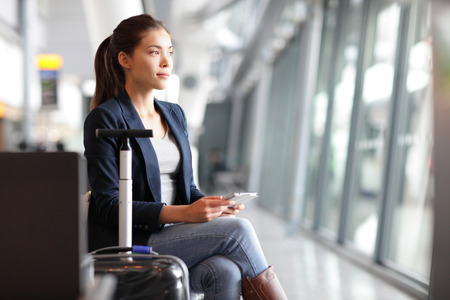gente aeropuerto: Pasajeros viajando mujer en el aeropuerto esperando por el transporte a�reo mediante la tableta del tel�fono inteligente. Mujer de negocios joven sonriente que se sienta con la maleta del recorrido de la carretilla, en pasillo que espera de la sala de embarque en el aeropuerto. Foto de archivo