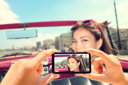 tomando: Tirar fotos com o telefone inteligente da mulher no carro. Close up da c