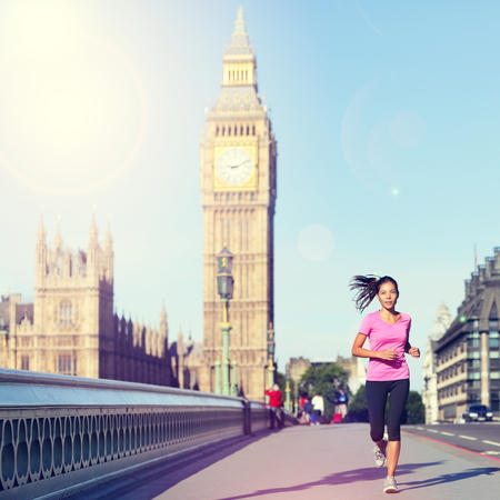 London woman running Big Ben - England lifestyle. Female runner jogging training in city with red double decker bus. Fitness girl smiling happy on Westminster Bridge, London, England, United Kingdom.