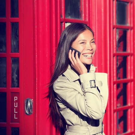 cell phone booth: London woman on smart phone by red phone booth. Young casual female business woman having conversation on mobile smart phone in London, England, United Kingdom. Multiracial Asian Caucasian model