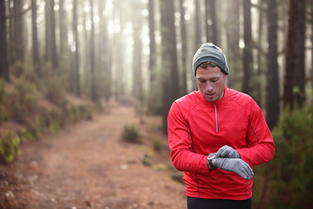 forest trail: Trail runner man looking at heart rate monitor watch running in cold forest wearing hat and gloves. Male jogger running training in woods.