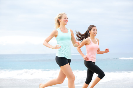 Runners - two women running outdoors training. Exercising female athletes jogging outside on beach smiling happy. Multiracial Asian and Caucasian woman in healthy lifestyle. photo