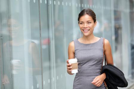 ビジネスの女性が飲むコーヒーを歩きます。弁護士専門または類似した歩行屋外幸せ持株使い捨て紙コップ。多民族アジアコーカサス実業家幸せな