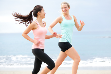 Exercise running women jogging happy on beach training as part of healthy lifestyle. Two fit female runners talking happy and smiling during workout. Multiracial Asian and Caucasian woman.