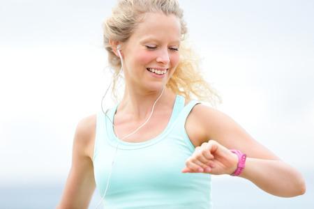 Mujer corriente que mira el monitor de ritmo cardíaco reloj fuera a correr en la playa. Fitness corredor entrenamiento Mujer joven corredora al aire libre escuchando música en los auriculares. Hermosa joven rubia de unos 20 años Foto de archivo