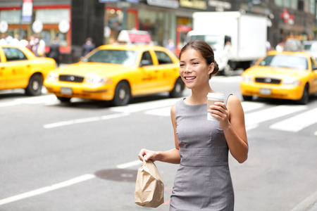 Business woman in New York City candid and real. Businesswoman in Manhattan walking in dress suit holding doggy bag drinking coffee smiling happy. Young multiracial Asian Caucasian professional female