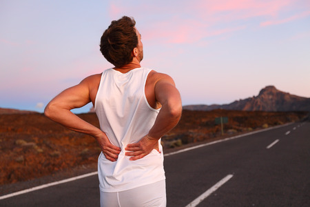 lower back pain: Back pain. Athletic running man with injury in sportswear rubbing touching lower back muscles standing on road outside at night.