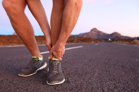injure: Twisted angle - running sport injury. Male athlete runner touching foot in pain due to sprained ankle.