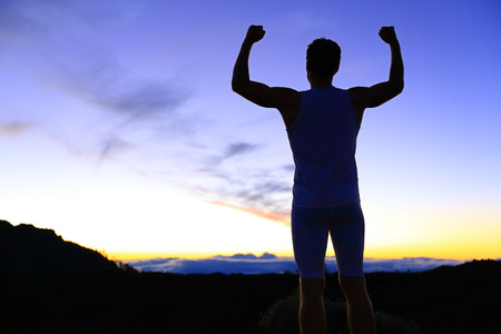 back up: Strength - strong success fitness man flexing muscles showing power pose outside in silhouette at night. Muscular fit male fitness man celebrating success macho style.