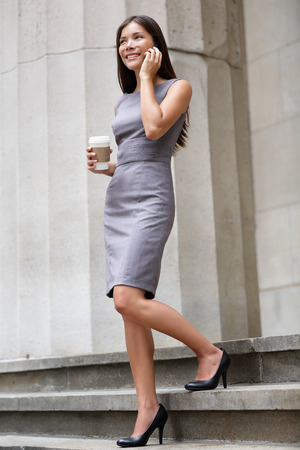 Business woman lawyer professional walking outdoors talking on cell smart phone drinking coffee from disposable paper cup. Multiracial Asian  Caucasian businesswoman smiling happy outside. photo