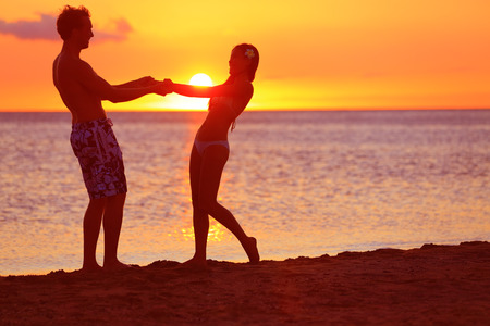 Romantic couple fun on beach sunset during travel. Happy woman and man holding hands playful on honeymoon romance in beautiful sun light. Multiracial couple, Image from Big Island, Hawaii. Фото со стока