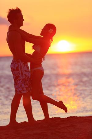 ロマンチックなカップルが旅行のビーチの夕日にキスします。幸せな女と男にキスを受け入れる新婚旅行の美しい太陽の光の中でのロマンス。多民
