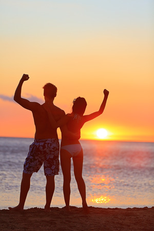Fitness couple cheering at beach sunset. Happy romantic fit young couple enjoying sunset with arms raised up flexing muscles together. People on sports vacation getaway. photo