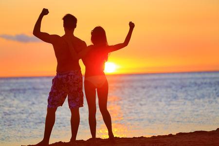 スポーティなフィットネス カップルのビーチの夕日で応援します。幸せなロマンチックなフィットの腕の筋肉が一緒にうごめくを調達の夕日を楽し