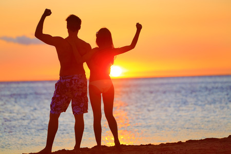 Sporty fitness couple cheering at beach sunset. Happy romantic fit young couple enjoying sunset with arms raised up flexing muscles together. People on sports vacation getaway.
