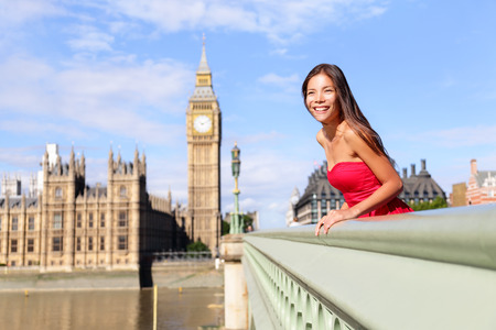city of westminster: London - happy woman by Big Ben in England. Beautiful tourist girl sightseeing travel on Westminster Bridge, London, England, United Kingdom. Multiracial Asian Caucasian female model travelling.