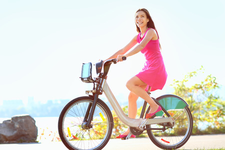 Girl biking in city park on bicycle. Happy woman on bike cycling outdoors in summer smiling of joy during outdoor activity. Mixed race Caucasian Asian female model.