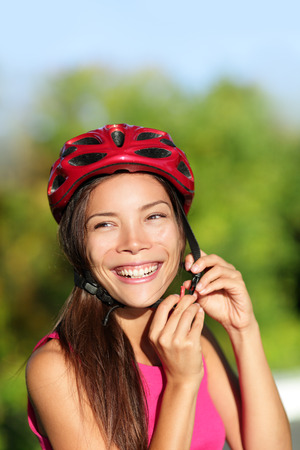 Biking helmet - woman putting bicycle helmet outside. Asian girl on bike, close up of helmet and face. Beautiful mixed race Caucasian Asian female outside. photo