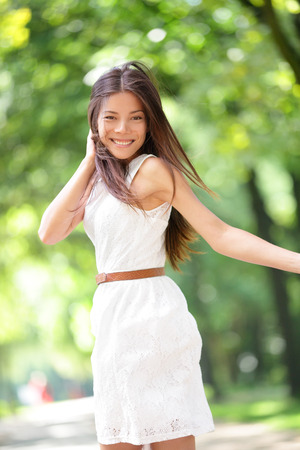 Asian woman happy running in summer  spring city park joyful and smiling in white sundress around trees. Beautiful fresh multiracial Asian Caucasian girl female model in her 20s outside. photo
