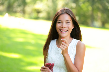 goji berry: Woman eating goji berries healthy food snack outdoors in park. Healthy eating and lifestyle with beautiful mixed race Asian Caucasian female girl model. 20s Stock Photo