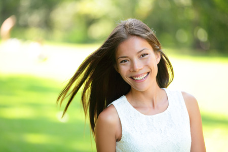 mixed race ethnicity: Asian girl spring portrait in park. Smiling happy mixed race Asian Caucasian woman in 20s looking at camera. Stock Photo