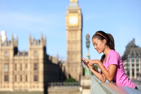 London lifestyle woman runner listening to music on smart phone near Big Ben. Female running girl resting after training in city. Fitness girl smiling happy on Westminster Bridge, London, England, UK. Stock Photo